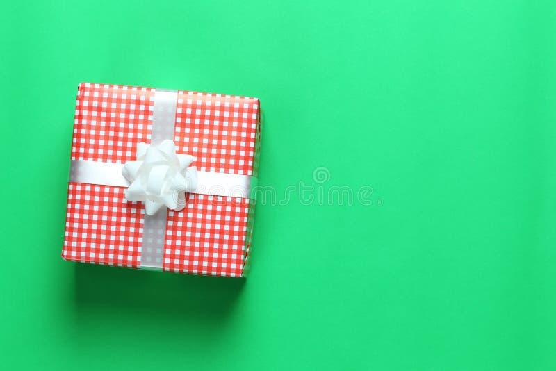 在一绿色加工印刷纸地板和hav安置的红色圣诞礼物箱子 库存照片