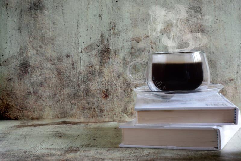 在一美丽的透明杯的热的咖啡有玻璃茶碟的在书站立,位于葡萄酒灰色背景 库存照片