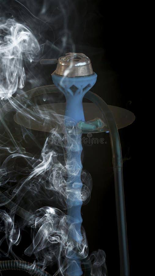 在一股黑背景和透明烟的蓝色水烟筒包围了他 库存照片