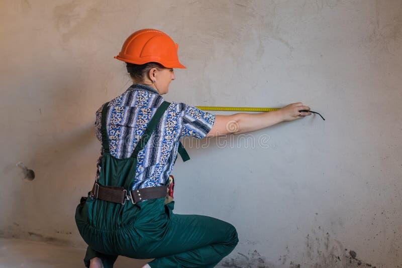 在一致的测量的墙壁的妇女建造者有磁带的 免版税库存照片