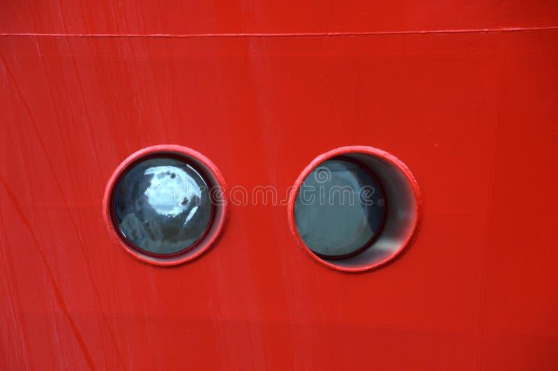 在一艘红色金属船的两扇小的红色舷窗 免版税库存照片