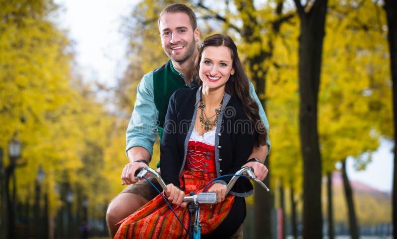 在一起少女装和皮革长裤的夫妇在自行车 免版税库存照片
