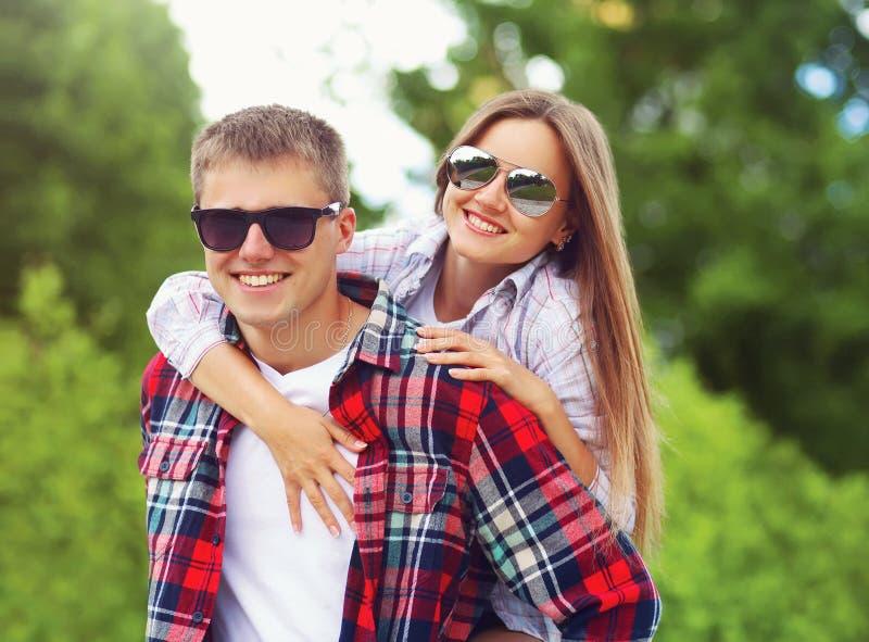 在一起拥抱的太阳镜的愉快的甜微笑的夫妇获得乐趣在夏天 免版税库存图片