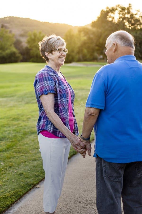 在一起步行的一对爱恋的资深夫妇在日落 免版税库存图片