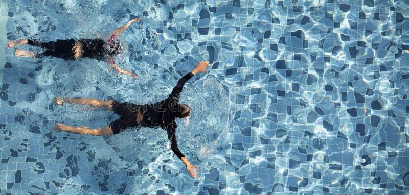 在一起水池的两个男孩游泳 免版税图库摄影