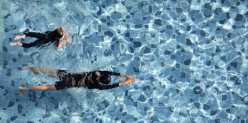 在一起水池的两个男孩游泳 免版税库存照片