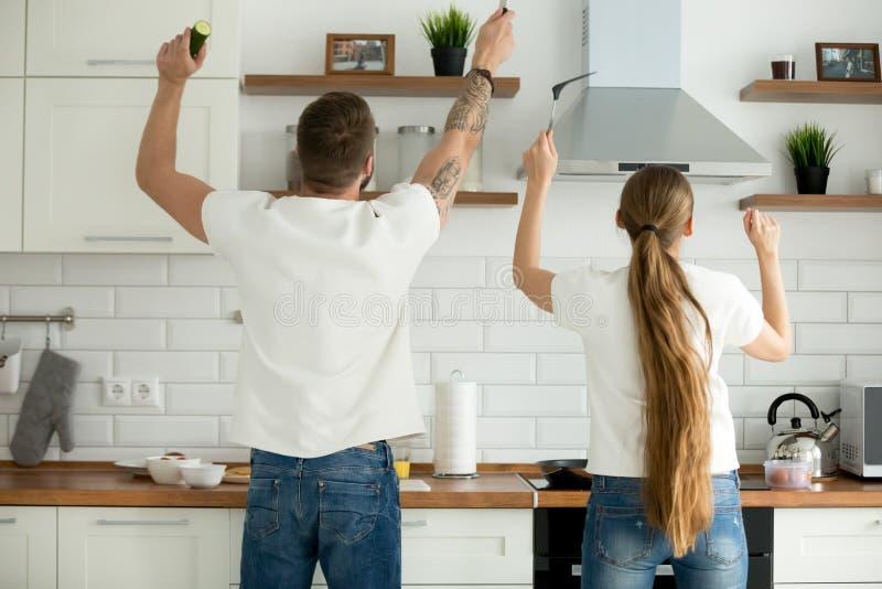 在一起烹调早餐的夫妇的背面图在厨房里 库存图片