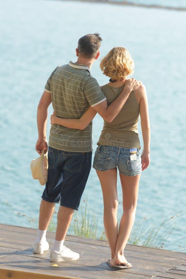 在一起站立在湖附近的爱的年轻夫妇 库存图片