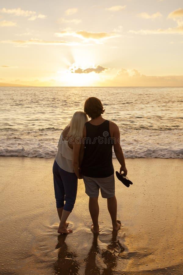 在一起观看日落的爱的夫妇在海滩 免版税库存照片