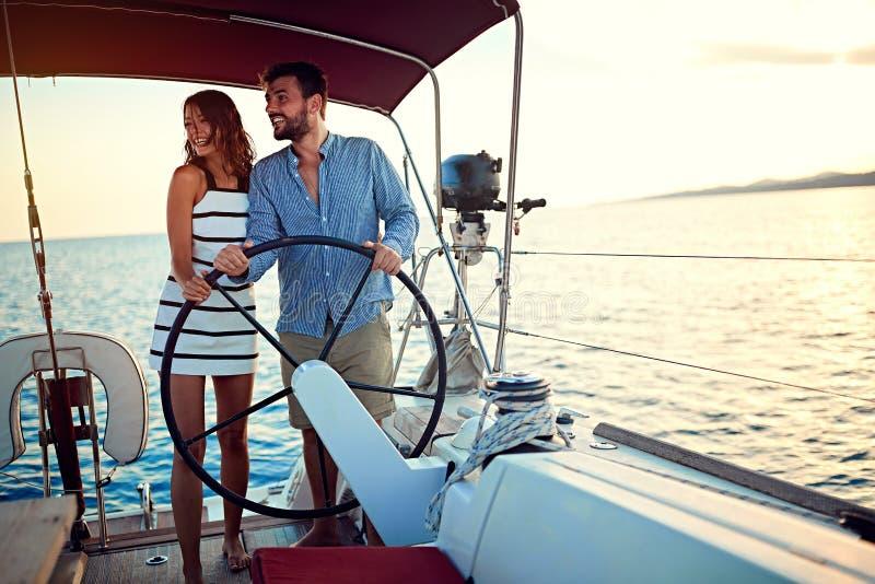 在一起豪华小船的夫妇航行和享用在日落 免版税图库摄影