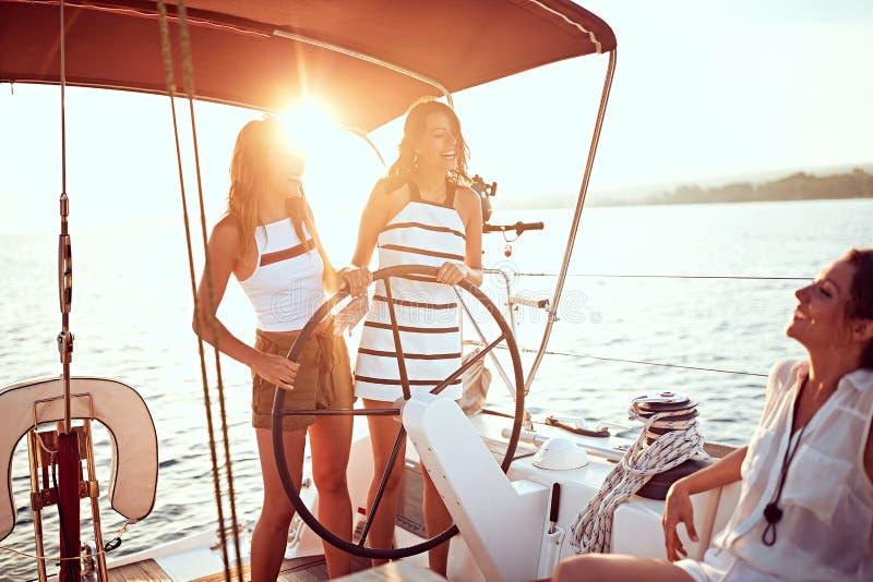 在一起豪华小船的少女航行和享用在日落 免版税库存照片