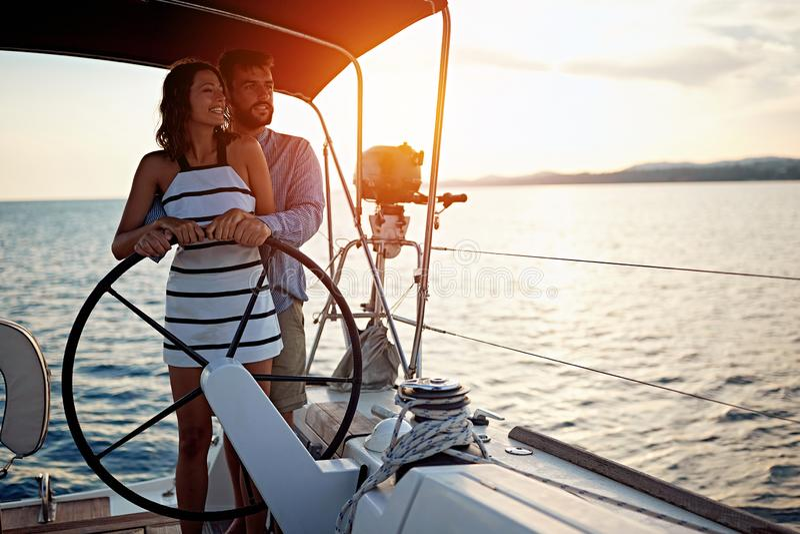 在一起豪华小船的浪漫夫妇航行和享用在日落 免版税图库摄影