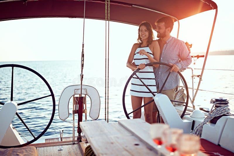 在一起豪华小船的浪漫男人和妇女航行和享用在日落 库存图片