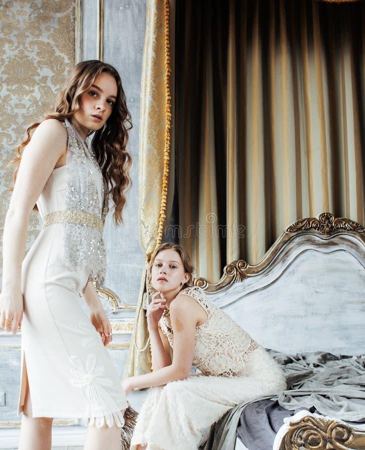 在一起豪华房子内部的两种相当双姐妹白肤金发的卷曲发型,富有的青年人概念 免版税库存照片