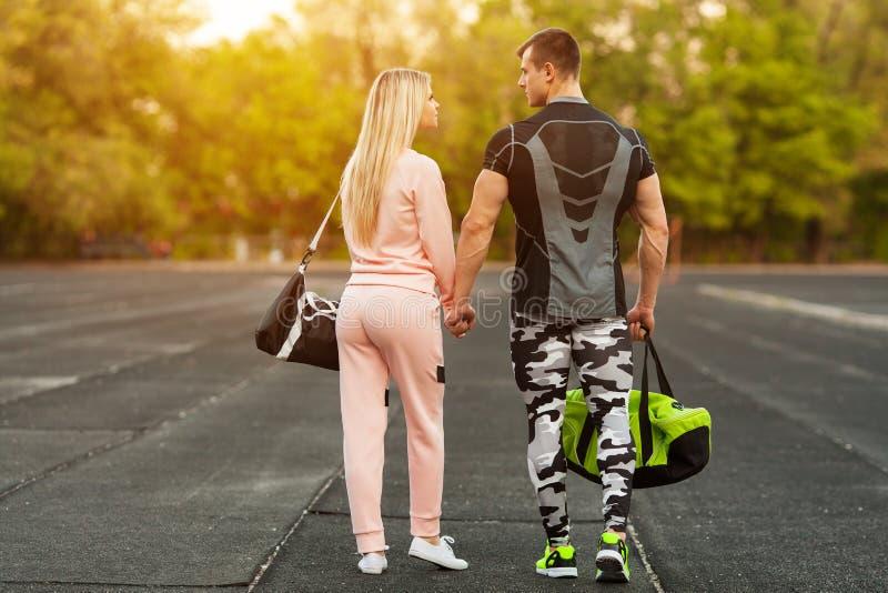 在一起走在体育场内的运动服的运动的夫妇 运动男人和妇女 库存照片