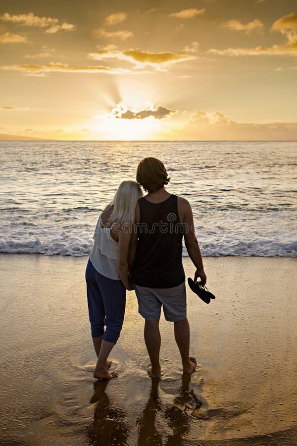 在一起走沿海滩的爱的夫妇在日落 图库摄影