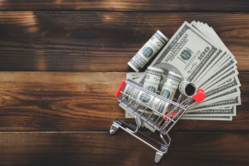 在一辆小型超市台车的金钱在老木背景 货币业务购物的财务概念 库存图片