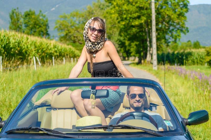 在一辆敞篷车汽车的一对年轻夫妇 免版税图库摄影