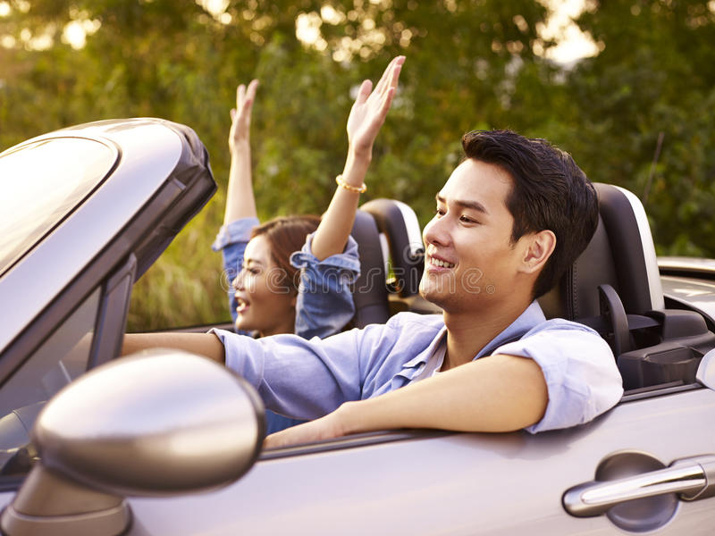 在一辆敞篷车汽车的年轻亚洲夫妇骑马 免版税库存图片