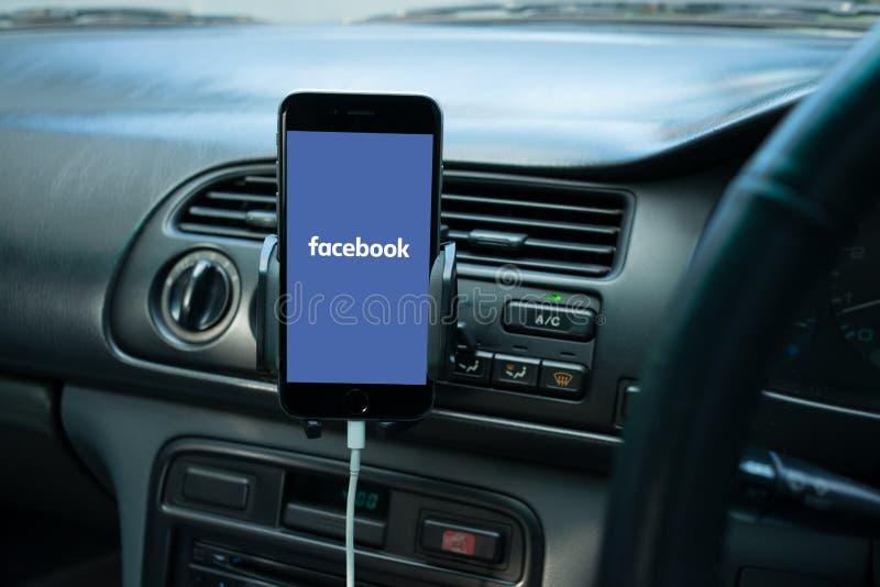 在一辆普通汽车的仪表板登上的智能手机 库存图片