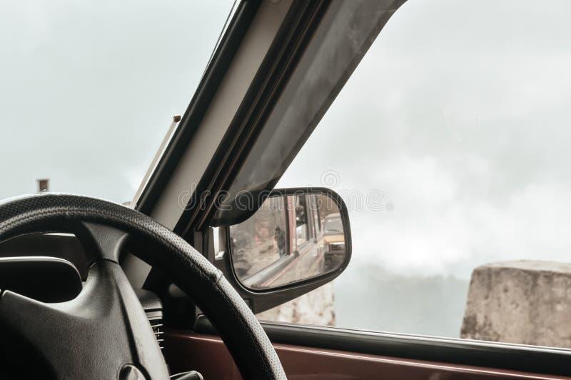 在一辆汽车的旁边后视镜在乡下路 免版税图库摄影