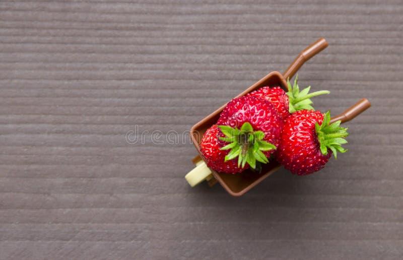 在一辆灰色木背景独轮车上用莓果红色草莓草莓安置题字 免版税库存图片