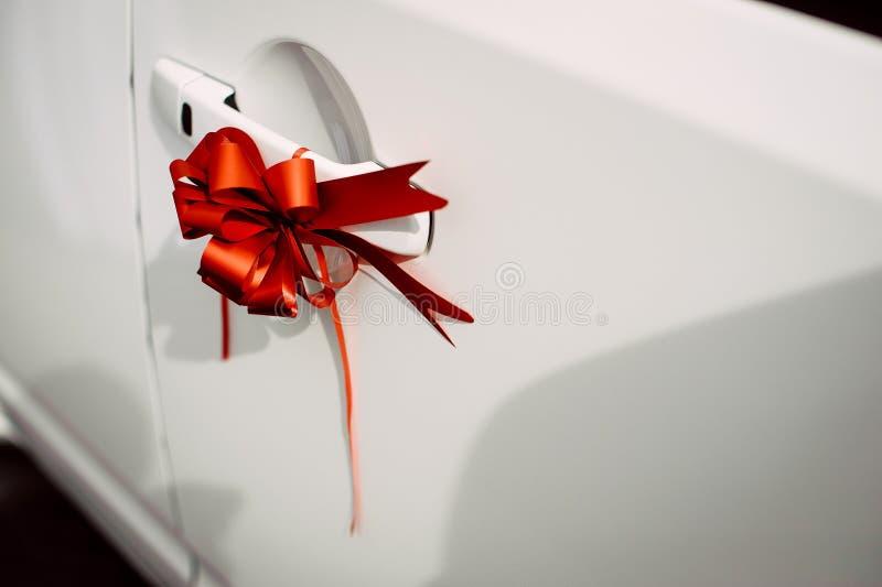 在一辆白色汽车的门把手的红色丝带弓 免版税库存照片
