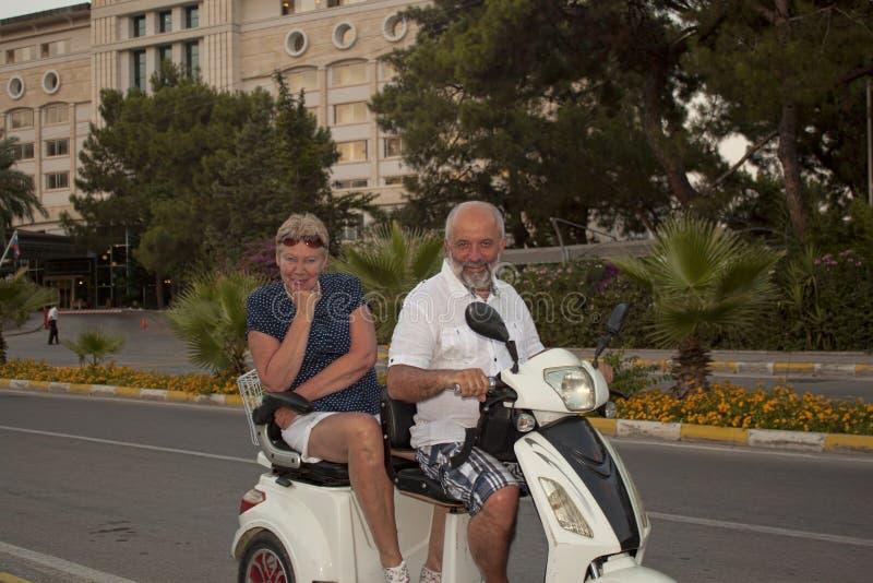 在一辆租用的滑行车的愉快的已婚夫妇 库存图片