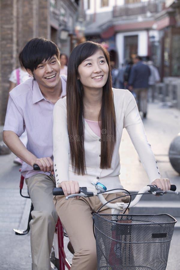 在一辆纵排自行车的年轻异性爱夫妇在北京 免版税库存图片