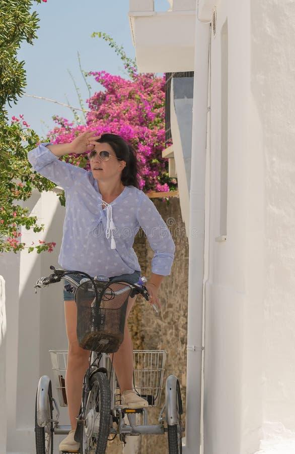 在一辆自行车顶部的妇女她的在安德罗斯海岛的假期在希腊 库存照片