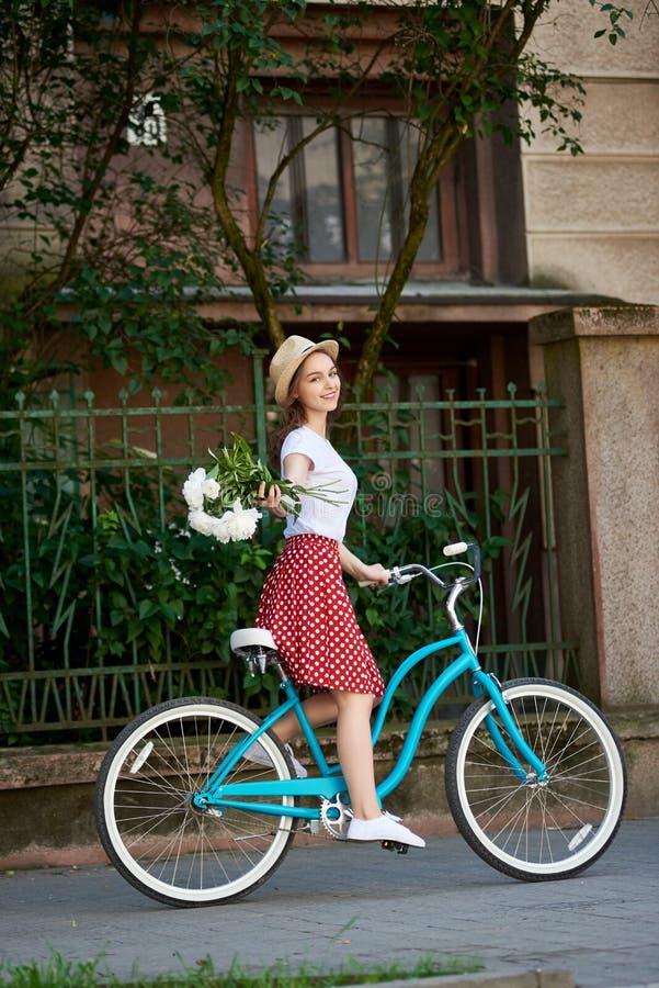 在一辆蓝色减速火箭的自行车的浪漫年轻自然舒展牡丹 库存照片
