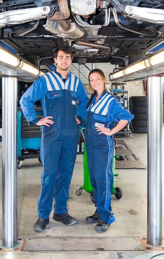 在一辆车下的两位汽车修理师在一辆水力汽车举 图库摄影