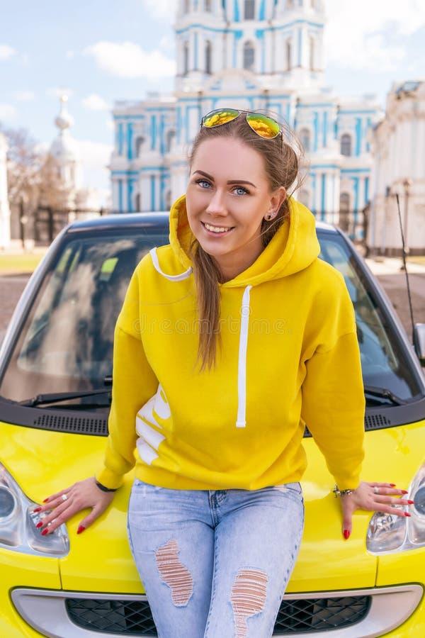 在一辆黄色汽车附近的愉快的妇女在一个救生服的城市 库存图片