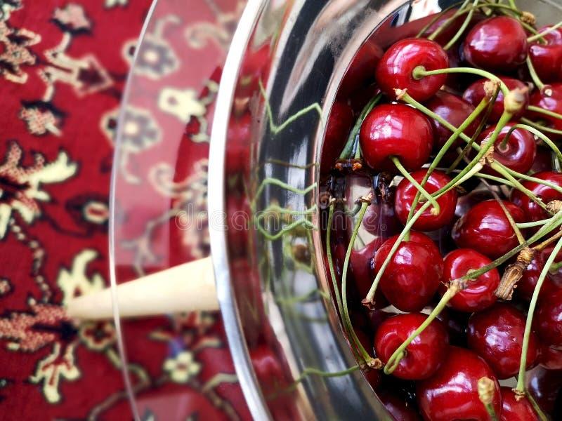 在一金属片的甜成熟樱桃在玻璃桌上 免版税库存图片