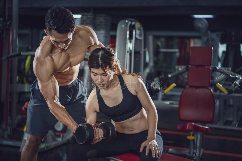 在一间健身房的年轻女人锻炼在她的个人教练员帮助下,行使与他的客户的健身辅导员在健身房 免版税库存图片