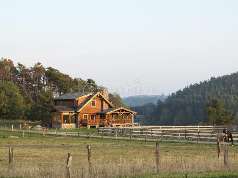 在一间木客舱附近的木篱芭在大农场 库存图片