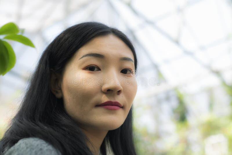 在一间热带温室里面的中国妇女 库存图片
