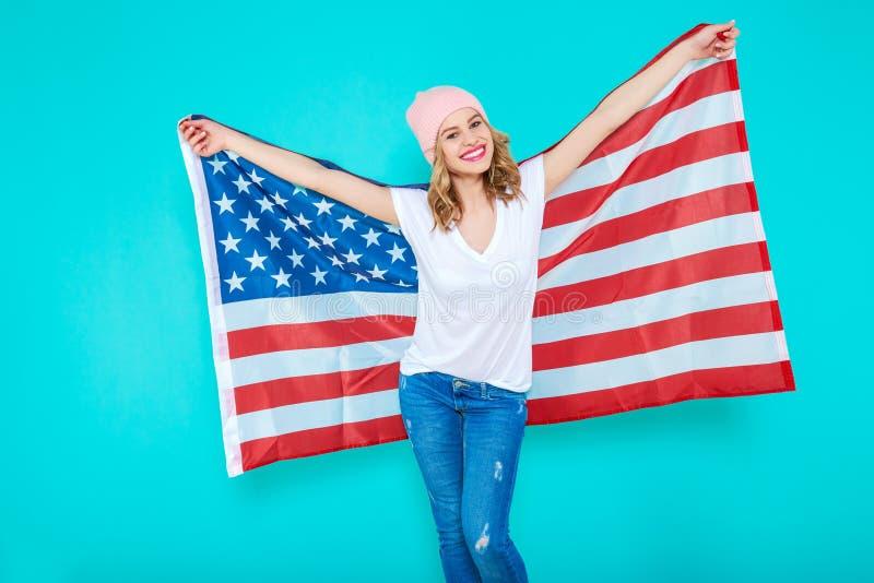 在一面美国国旗和白色T恤杉的愉快的年轻微笑的妇女包裹的牛仔裤,做和平标志和看照相机 免版税图库摄影