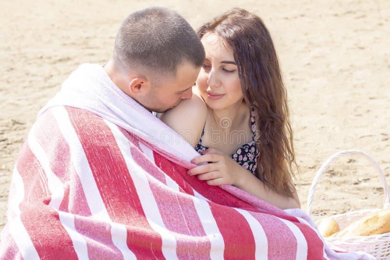 在一顿夏天野餐在海,在毯子包裹的休息的年轻夫妇 夏天野餐,会议,爱 图库摄影