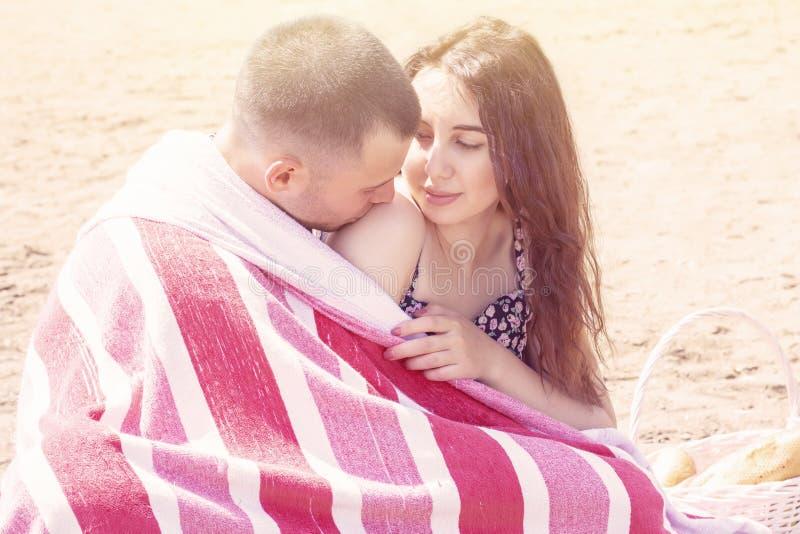 在一顿夏天野餐在海,在毯子包裹的休息的年轻夫妇 夏天野餐,会议,爱 库存照片