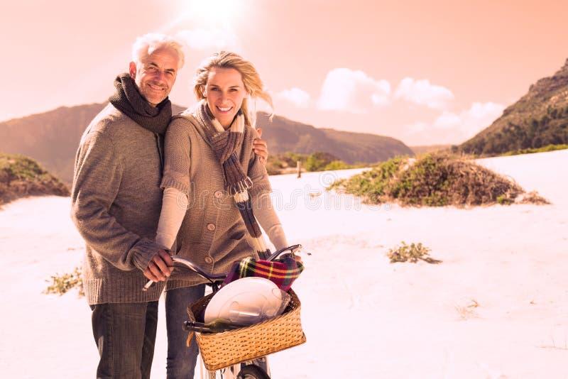 去在一顿自行车乘驾和野餐的无忧无虑的夫妇在海滩 皇族释放例证