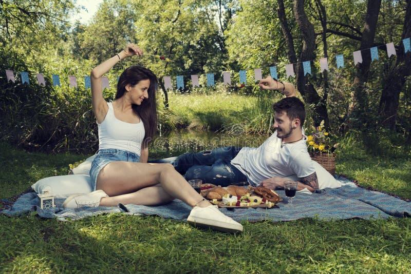 在一顿野餐的年轻夫妇在城市公园坐一揽子和决斗与串用果子 库存照片