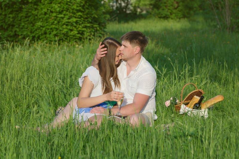 在一顿野餐的年轻夫妇在城市停放 免版税库存图片
