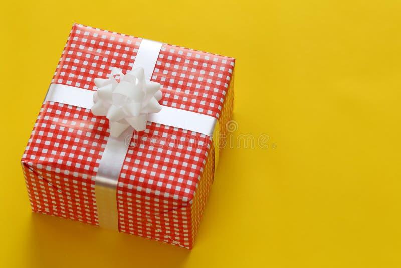 在一黄色加工印刷纸地板和ha安置的红色圣诞礼物箱子 图库摄影