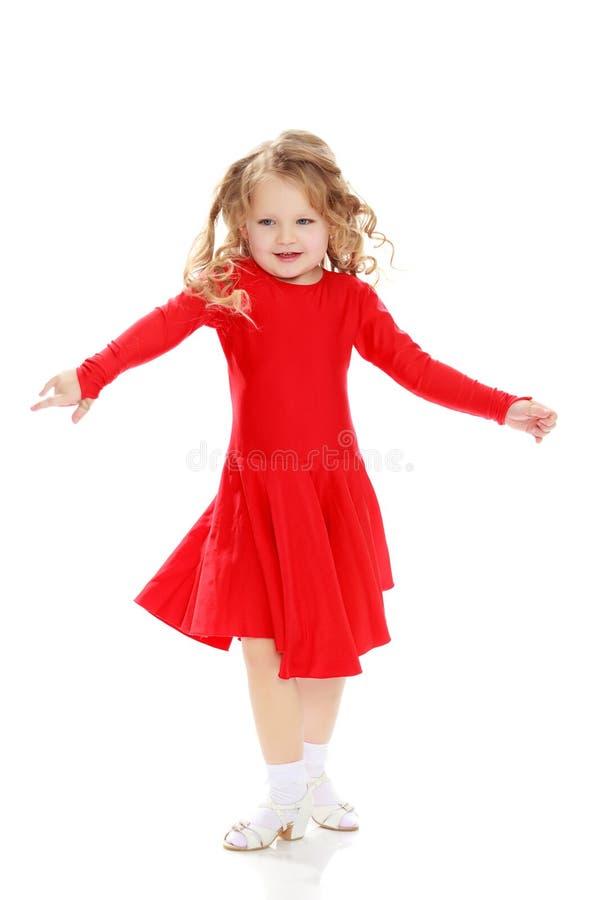 在一件明亮的红色礼服的女孩跳舞 库存图片