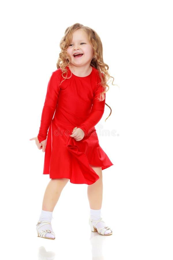 在一件明亮的红色礼服的女孩跳舞 免版税库存图片
