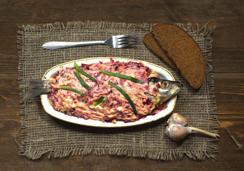 在一件皮大衣下的沙拉鲱鱼在backgro的一张木桌上 免版税库存图片