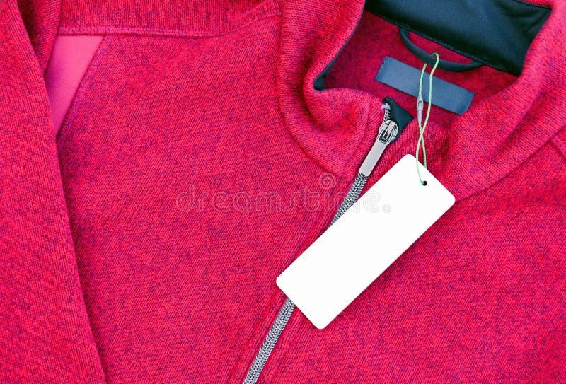 在一件红色夹克的空白的衣物标签标记 图库摄影