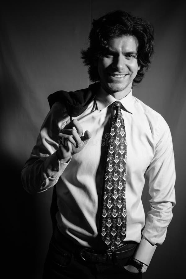 在一件衬衣的年轻人商人有领带微笑和举行的在后面后的一件夹克 免版税库存图片