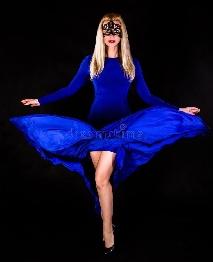 在一件长的蓝色晚礼服的美好的少妇跳舞 图库摄影